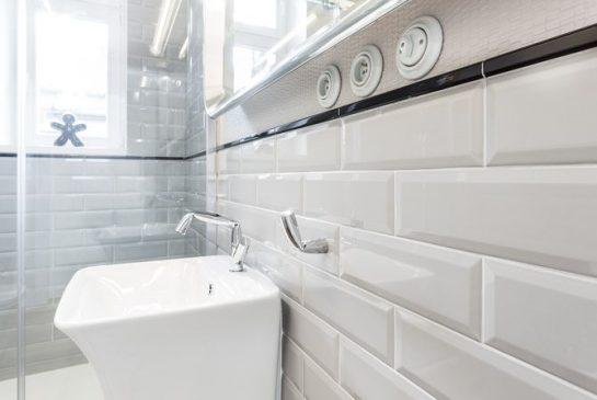 W łazience udało się sprytnie połączyć estetykę dwóch epok. Na ścianach, do poziomu lamperii, położono szare płytki cegiełki, ponad nimi leży, biegnąca aż pod sufit, gumowa w strukturze, nowoczesna okleina marki Vescom.